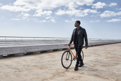 Man with bike on waterfront promenade - JND00045