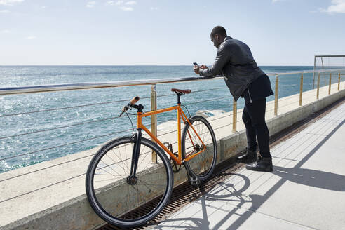 Man with bike on waterfront promenade, using smartphone - JND00054