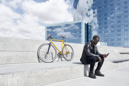 Man with yellow bicycle sitting on stairs, using smartphone, Barcelona, Spain - JND00057