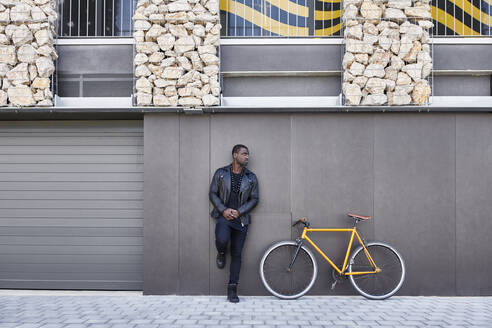 Man leaning on a wall next to his bike - JND00063