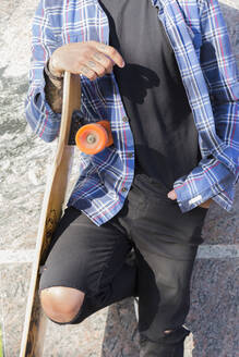 Tattooed young man with longboard leaning against wall, partial view - JPTF00130