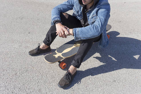 Tattooed young man sitting on longboard, partial view - JPTF00136