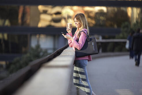 Young businesswoman using smartphone and holding coffee to go - JSRF00199