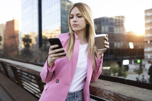 Young businesswoman using smartphone and holding coffee to go - JSRF00202