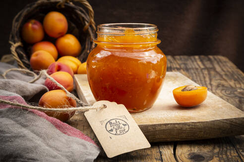 Apricot jam and apricots, sign 'made with love' on dark wood - LVF08084