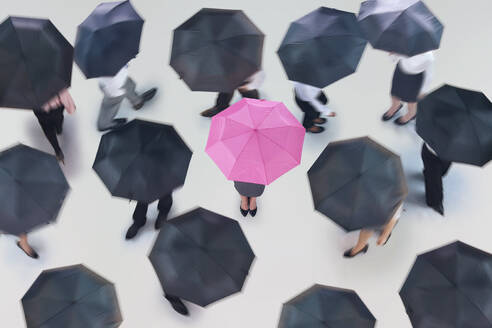 Businesswoman with pink umbrella surrounded by business people walking with black umbrellas - JUIF01316
