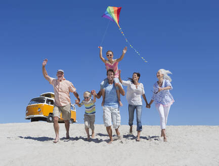 Happy multi-generation family with kite running and waving on sunny beach with van in background - JUIF01334