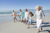 Portrait of happy multi-generation family holding hands and running on sunny beach - JUIF01352