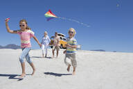 Grandparents and grandchildren running with kite on sunny beach with van in background - JUIF01355