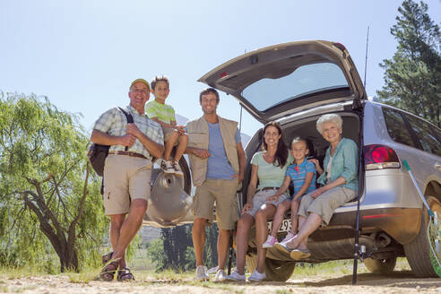 Portrait of smiling multi-generation family with fishing rods at back of car lakeside - JUIF01358