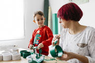 Mother and son doing crafts at home, painting cardboard rolls to make a Christmas tree - JRFF03243