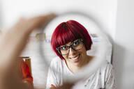 Portrait of a smiling woman through a roll of cardboard - JRFF03246