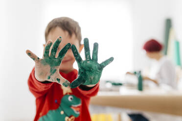 Boy showing his hands painted green while doing crafts at home - JRFF03252