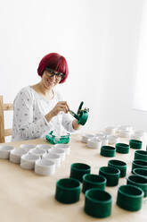 Woman painting a roll of cardboard with a green brush to make a Christmas tree - JRFF03255