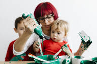 Mother with her children doing crafts at home and painting with green - JRFF03261