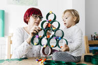 Mother and daughter doing crafts at home with accessories to make a Christmas tree - JRFF03267