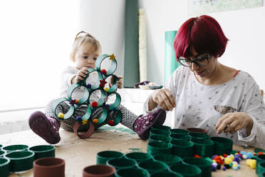 Mother and daughter doing crafts at home with accessories to make a Christmas tree - JRFF03270