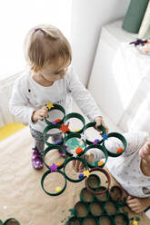 Mother and daughter doing crafts at home with accessories to make a Christmas tree - JRFF03273