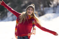 Young blond woman raising arms in winter - JSRF00230