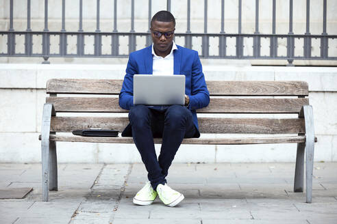 Young businessman wearing blue suit jacket sitting on bench and using laptop - JSRF00233