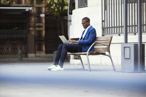 Young businessman wearing blue suit jacket sitting on bench and using laptop - JSRF00236