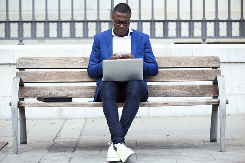 Young businessman wearing blue suit jacket sitting on bench and using laptop - JSRF00239