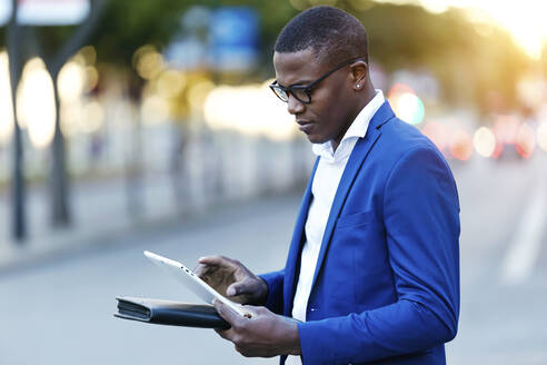 Young businessman wearing blue suit jacket and using his digital tablet at a street - JSRF00254