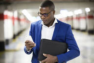 Young businessman wearing blue suit jacket and using smartphone - JSRF00263