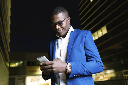 Young businessman wearing blue suit jacket and using smartphone at night - JSRF00266