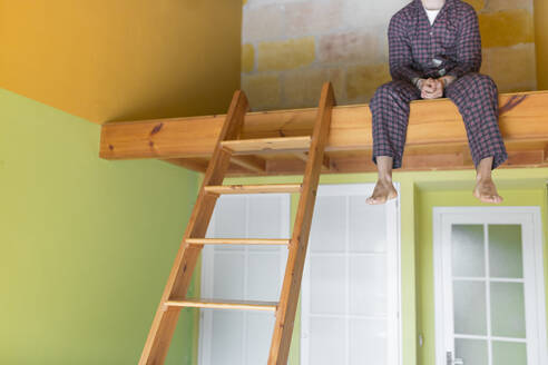 Man wearing a pyjama and sitting on loft bed at home - JPTF00143