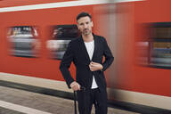 Mature man with trolley on station - PNEF01588