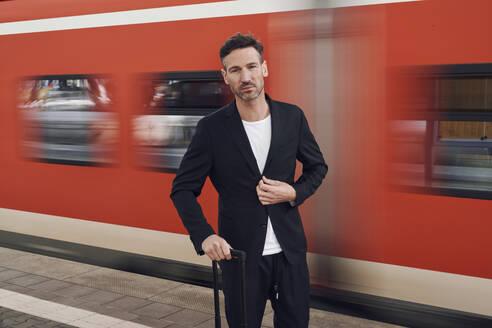 mittelalter Mann mit Koffer auf Bahnsteig vor vorbeifahrendem Zug, Deutschland - PNEF01588