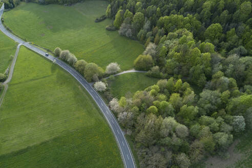 Abstract aerial view of rural road through landscape with agricultural fields, meadows and forest, springtime, Franconia, Bavaria, Germany - RUEF02245