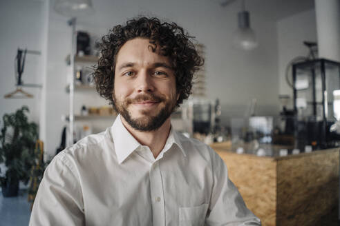 Smiling businessman in a coffee shop, portrait - KNSF05971