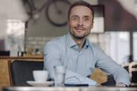Successful businessman sitting in coffee shop, smiling, drinking coffee - KNSF06028