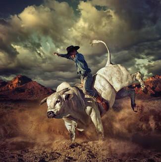 Caucasian cowboy riding bucking bull in desert - BLEF06729