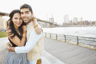 Indian couple hugging by New York city skyline, New York, New York, United States - BLEF06738