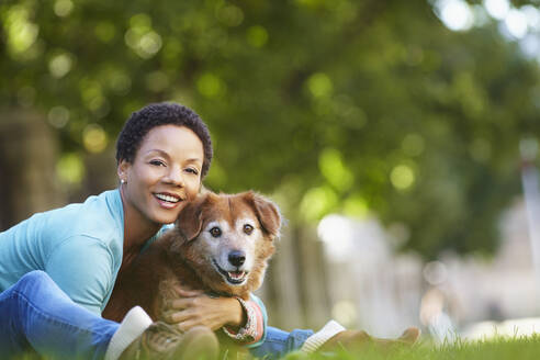 Black woman petting dog in park - BLEF06747