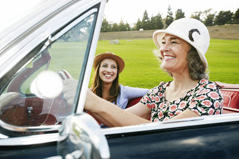 Mother and daughter driving in classic convertible - BLEF06846