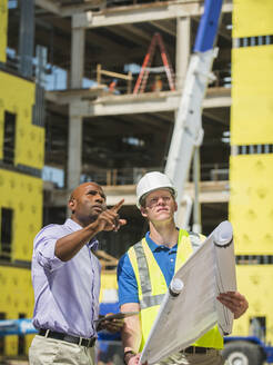 Businessman and construction worker reading blueprints at construction site - BLEF06864