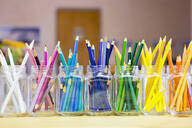 Close up of multicolor pencils organized in jars - BLEF06918