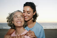 Caucasian mother and daughter hugging at beach - BLEF06981