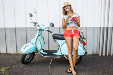 Woman eating shave ice near scooter - BLEF06987