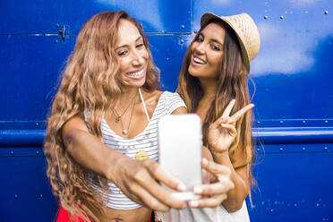 Women taking cell phone photograph together - BLEF06990