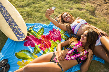 Women taking cell phone photograph together on blanket - BLEF06996