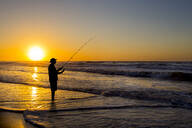 Silhouette of man fishing in waves on beach at sunset - MINF12334