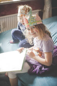 Two sisters wearing crowns and unpacking presents on bed - IHF00107
