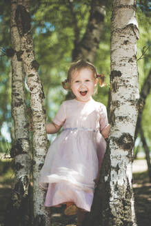 Portrait of happy little girl playing between birch trees - IHF00119