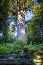 Woman looking at Te Matua Ngahere, a giant kauri tree, Waipoua Forest, Westcoast Northland, North Island, New Zealand - RUNF02697