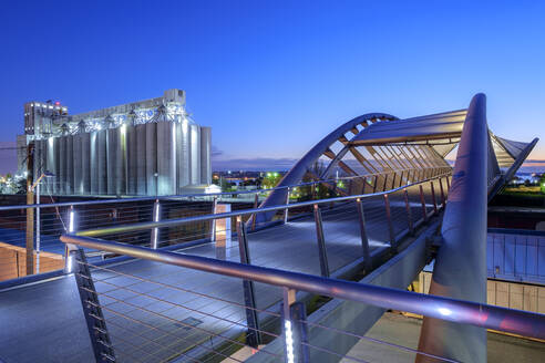 Pedestrian bridge and factory lit up at night - MINF12482